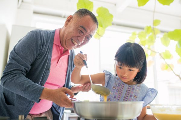 Grandfather smiling and helping his granddaughter to make breakfast in the kitchen. Kyoto, Japan. May 2016